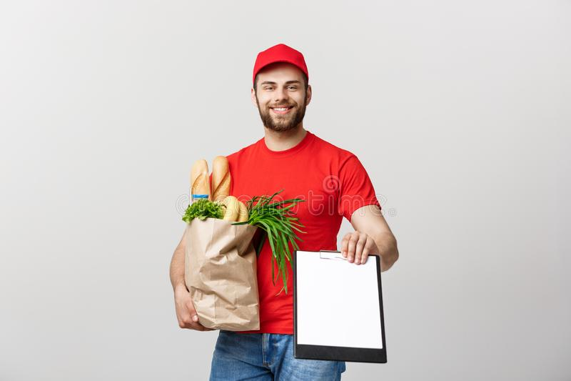 Delivery Concept: Handsome Caucasian grocery delivery courier man in red uniform with grocery box with fresh fruit and stock photos