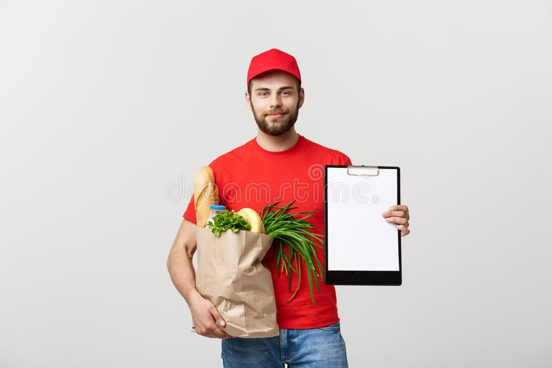 Delivery Concept: Handsome Caucasian grocery delivery courier man in red uniform with grocery box with fresh fruit and stock photo