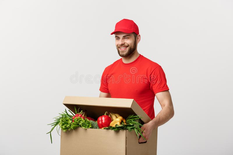 Delivery Concept: Handsome Caucasian grocery delivery courier man in red uniform with grocery box with fresh fruit and royalty free stock image