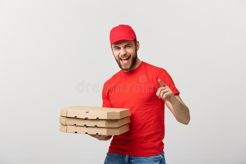 Delivery Concept: Handsome pizza delivery man courier in red uniform with cap holding pizza boxes. Isolated on white. Delivery Concept: Handsome pizza delivery royalty free stock image