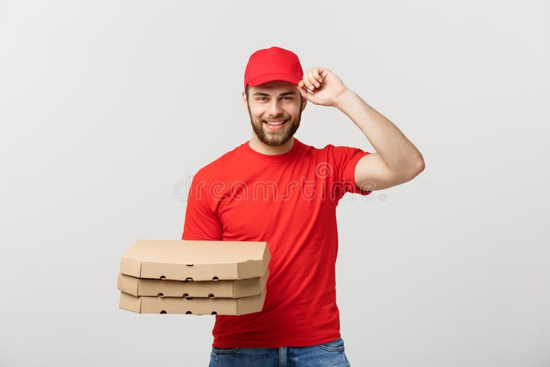 Delivery Concept: Handsome pizza delivery man courier in red uniform with cap holding pizza boxes. Isolated on white. Delivery Concept: Handsome pizza delivery royalty free stock photo