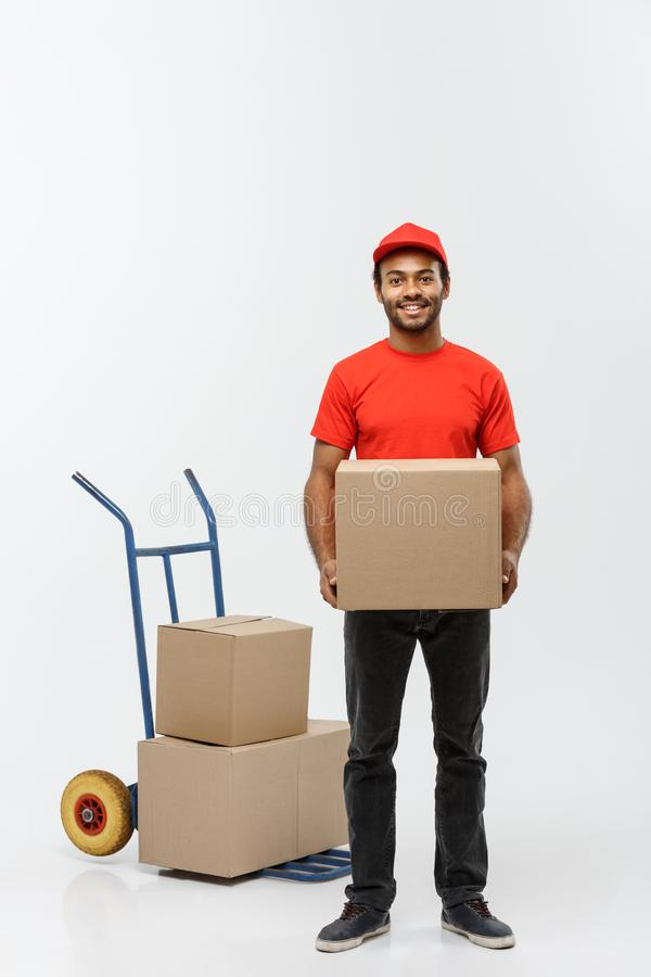 Delivery Concept - Portrait of Handsome African American delivery man or courier with hand truck and holding box. Isolated on Grey studio Background. Copy stock images