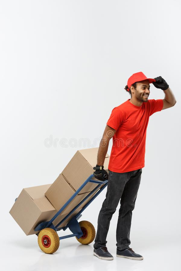 Delivery Concept - Portrait of Handsome African American delivery man or courier pushing hand truck with stack of boxes. Isolated on Grey studio Background royalty free stock photography