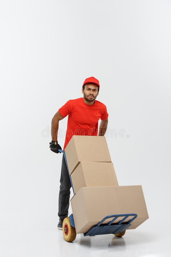 Delivery Concept - Portrait of Handsome African American delivery man or courier pushing hand truck with stack of boxes. Isolated on Grey studio Background royalty free stock photo