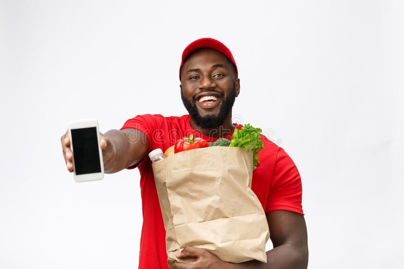 Delivery Concept - Portrait of Handsome African American delivery man or courier showing mobile phone on you to check. The order. Isolated on Grey studio royalty free stock photo
