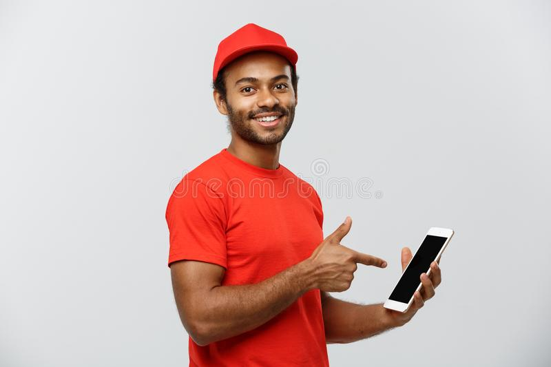 Delivery Concept - Portrait of Handsome African American delivery man or courier showing tablet on you to check the. Order. Isolated on Grey studio Background royalty free stock images