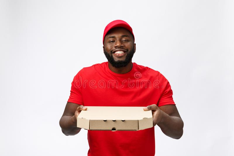 Delivery Concept - Portrait of Handsome African American Pizza delivery man. Isolated on Grey studio Background. Copy stock photography