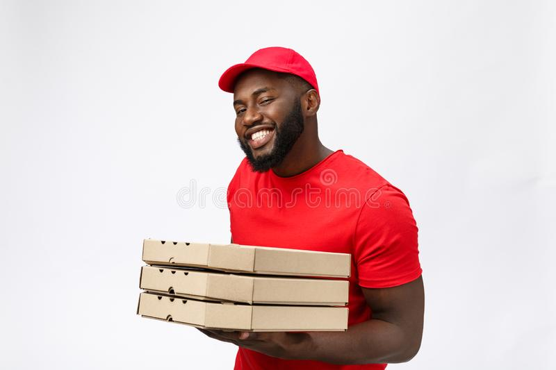 Delivery Concept - Portrait of Handsome African American Pizza delivery man. Isolated on Grey studio Background. Copy. Space stock photography