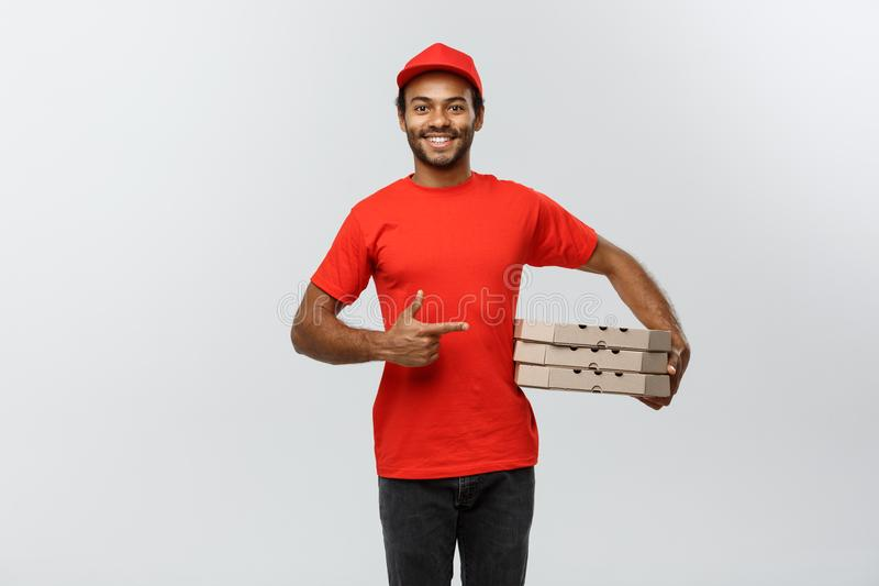 Delivery Concept - Portrait of Happy African American delivery man pointing hand to present a box package. Isolated on stock images