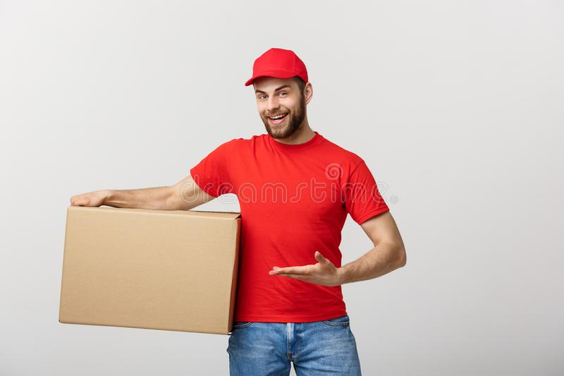 Delivery Concept - Portrait of Happy Caucasian delivery man pointing hand to present a box package. Isolated on Grey stock image