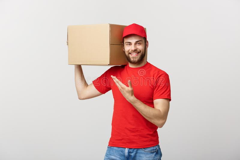 Delivery Concept - Portrait of Happy Caucasian delivery man pointing hand to present a box package. Isolated on Grey stock photography