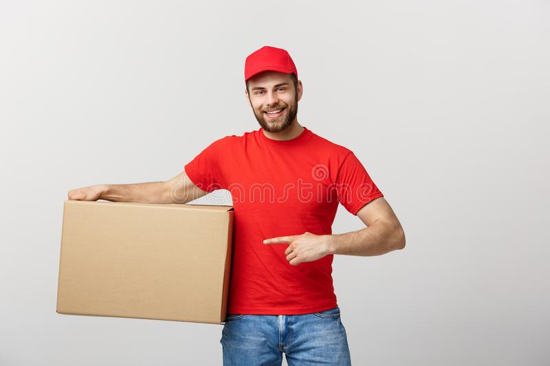 Delivery Concept - Portrait of Happy Caucasian delivery man pointing hand to present a box package. Isolated on Grey royalty free stock image