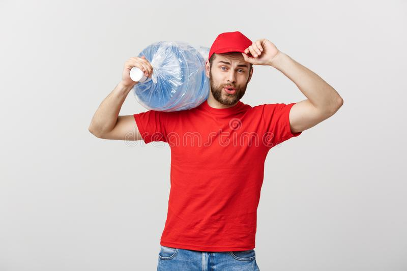 Delivery Concept: Portrait of smiling bottled water delivery courier in red t-shirt and cap carrying tank of fresh drink. Isolated over grey background royalty free stock photos