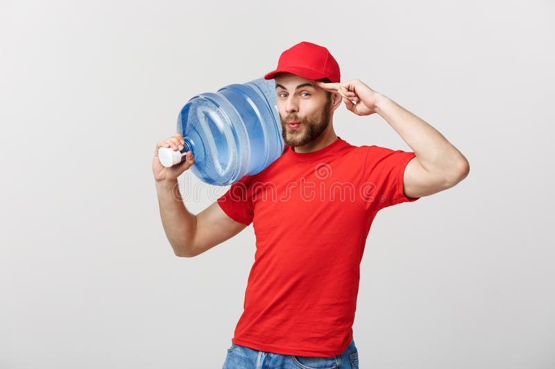 Delivery Concept: Portrait of smiling bottled water delivery courier in red t-shirt and cap carrying tank of fresh drink. Isolated over grey background royalty free stock photo