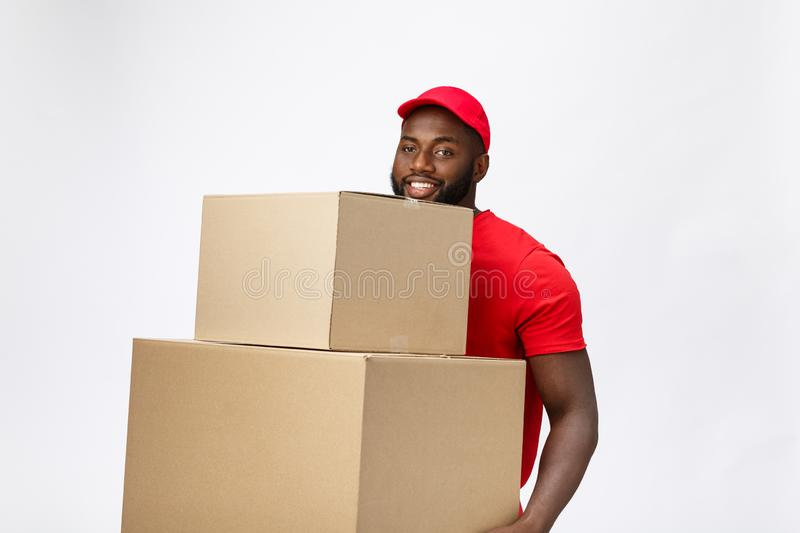 Delivery Concept - Side view Portrait of Happy African American delivery man in red cloth holding a box package. Isolated on Grey Background. Copy Space stock photo