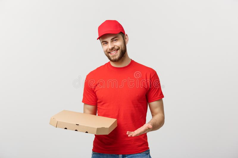 Delivery Concept: Young haapy caucasian Handsome Pizza delivery man holding pizza boxes isolated over grey background.  royalty free stock image