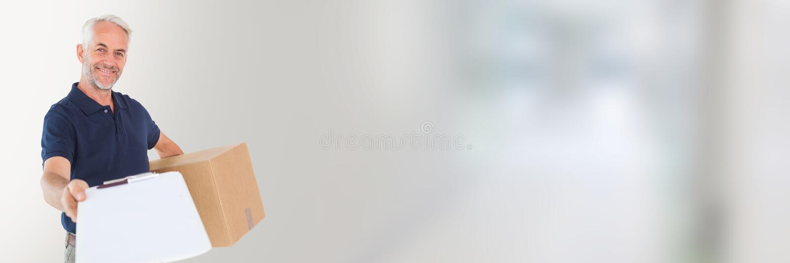 Delivery Courier holding box and form in front of blurred background. Digital composite of Delivery Courier holding box and form in front of blurred background royalty free stock image