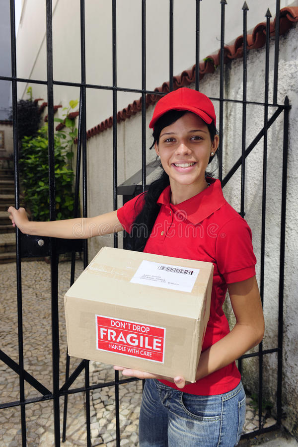 Delivery courier or mailman delivering package. Young delivery courier or mailman delivering package outdoors royalty free stock images