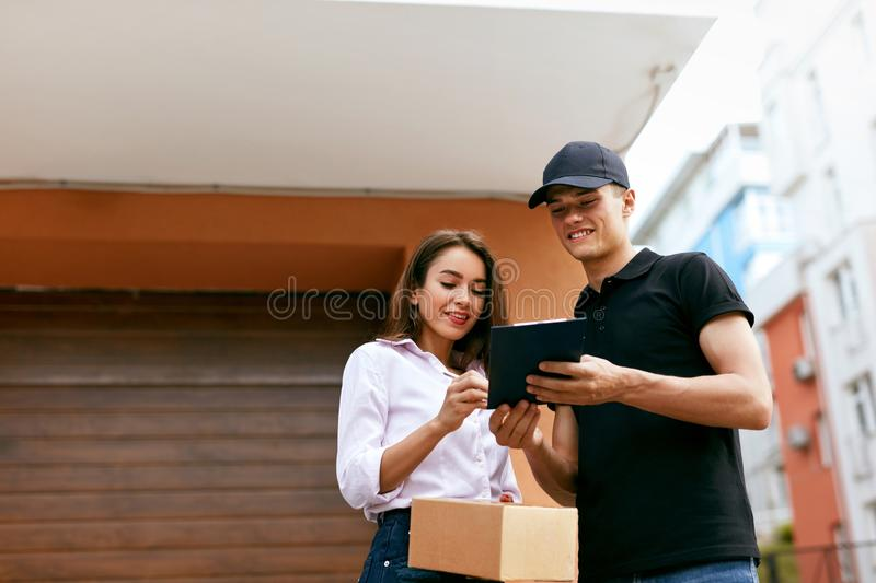 Delivery Courier. Man Delivering Package To Woman. Client Signing Delivery Documents. High Resolution stock photography