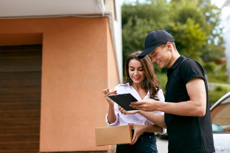 Delivery Courier. Man Delivering Package To Woman. Client Signing Delivery Documents. High Resolution stock images