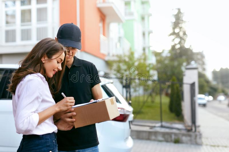 Delivery Courier. Man Delivering Package To Woman. Client Signing Delivery Documents. High Resolution stock photo
