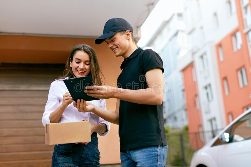 Delivery Courier. Man Delivering Package To Woman. Client Signing Delivery Documents. High Resolution stock image
