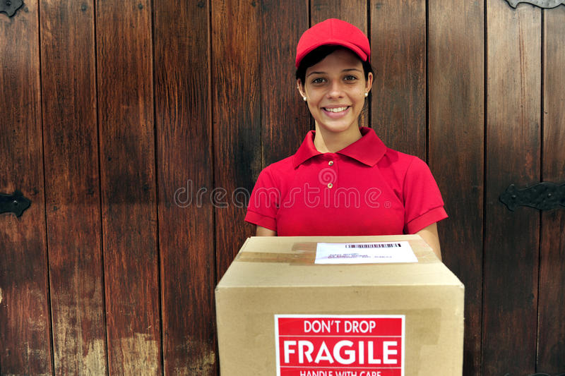Delivery courier with package. Young delivery courier delivering package in front of wooden door with copy space stock images