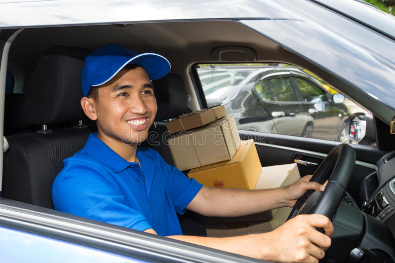 Delivery driver driving with parcels on seat royalty free stock image