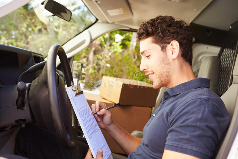 Delivery Driver Sitting In Van Filling Out Paperwork royalty free stock images