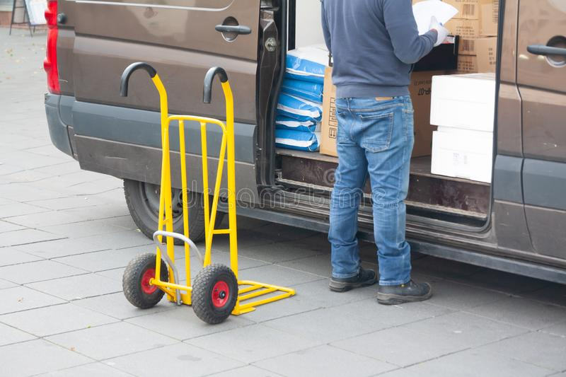 Delivery driver is unloading cargo van with goods to truck royalty free stock photos