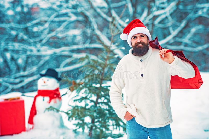 Delivery gifts. Cute little snowman and bearded man with shopping bag. Hipster santa claus. Funny snowman with shopping royalty free stock photo