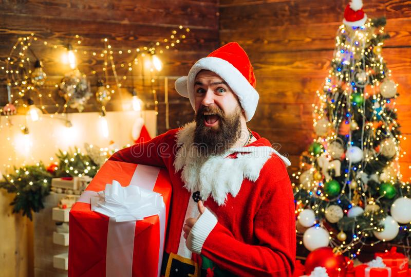 Delivery gifts. Gift emotions. Hipster in red Santa hat holding present. stock photography