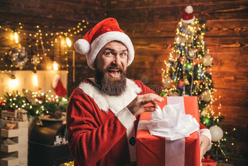 Delivery gifts. Gift emotions. Santa man holding gift. Crazy, funny Hipster Santa. royalty free stock image