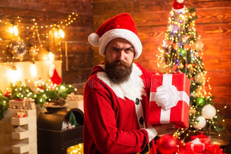 Delivery gifts. Gift emotions. Santa man holding gift. Hipster in red Santa hat holding present. stock photography