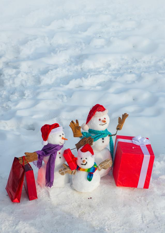 Delivery gifts. Snowman gifting. Snowman - father, mother and snowman - baby surprise outdoor. Snow man for sale stock photos