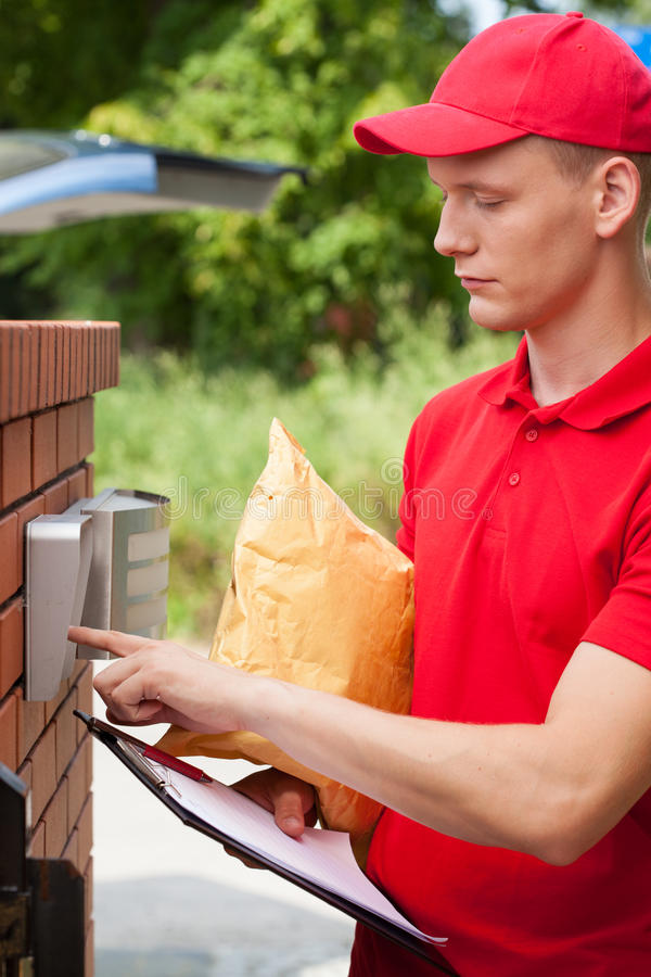 Delivery guy calling on entryphone royalty free stock photography