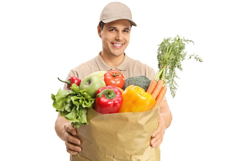 Delivery guy giving a bag of groceries. Isolated on white background stock photography