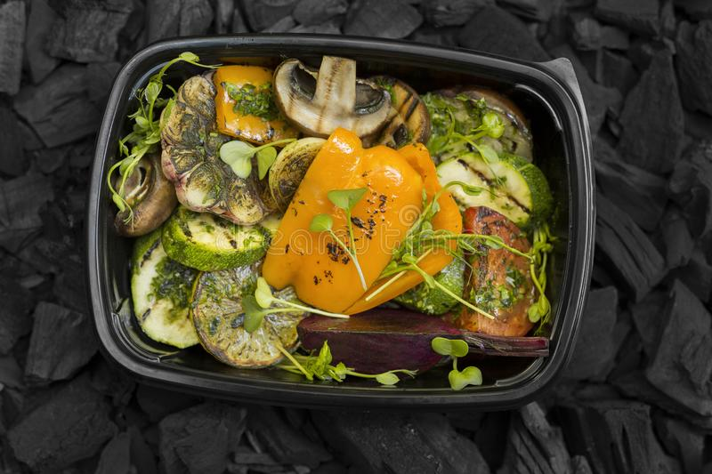 Grilled vegetables in take away black box on coals background royalty free stock photos