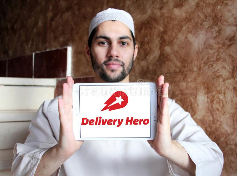 Delivery Hero online food delivery company logo. Logo of Delivery Hero company on samsung tablet holded by arab muslim man. Delivery Hero AG is a publicly listed royalty free stock photography