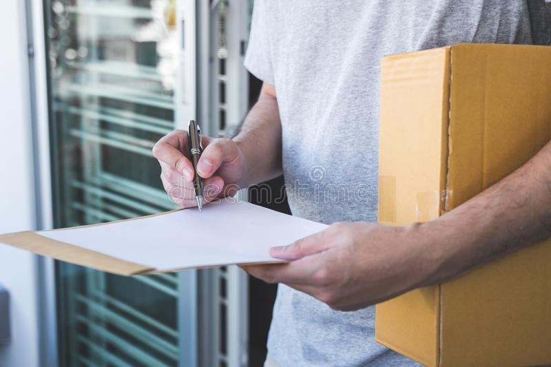Delivery mail man giving parcel box to recipient and signature form, Young owner signing receipt of delivery package from post. Shipment courier, Home delivery stock photography