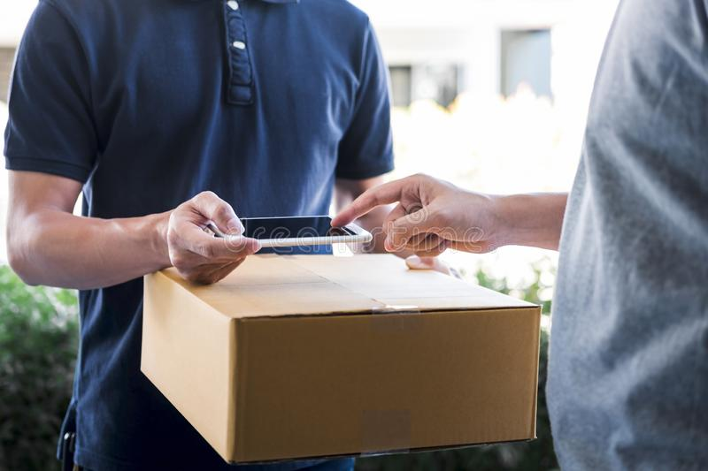 Delivery mail man giving parcel box to recipient, Young man appending signing in digital mobile phone receipt of delivery package. Delivery mail men giving stock photos