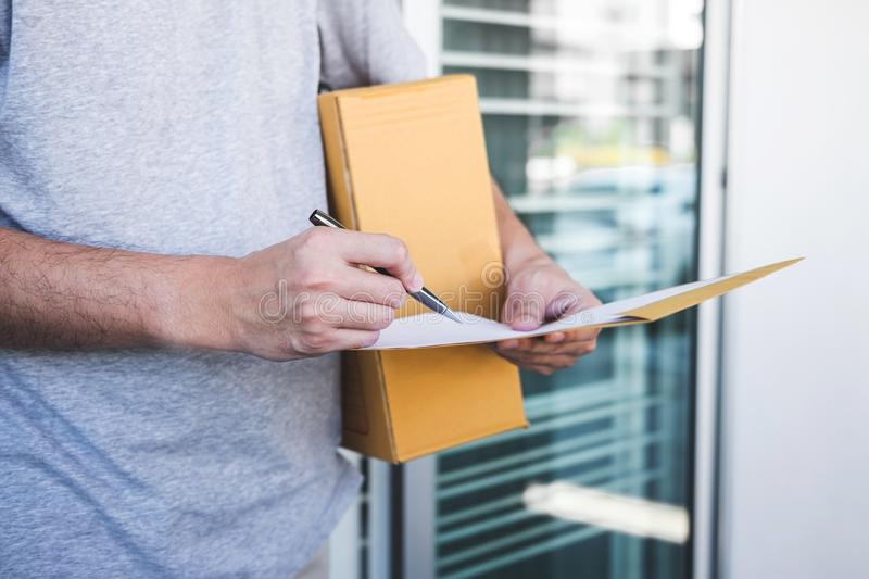 Delivery mail man giving parcel box to recipient, Young man signing receipt of delivery package from post shipment courier at home.  royalty free stock photo