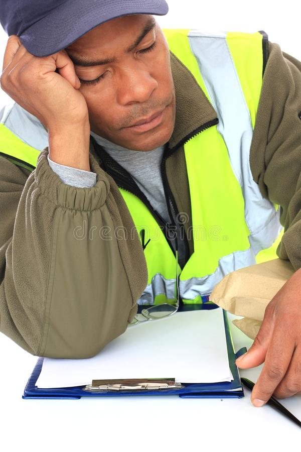 Delivery man. Image of a delivery man sleeping at work with hand supporting his head royalty free stock photo