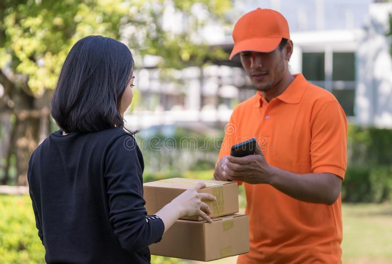 Delivery man asking woman to sign mobile for the delivery royalty free stock images