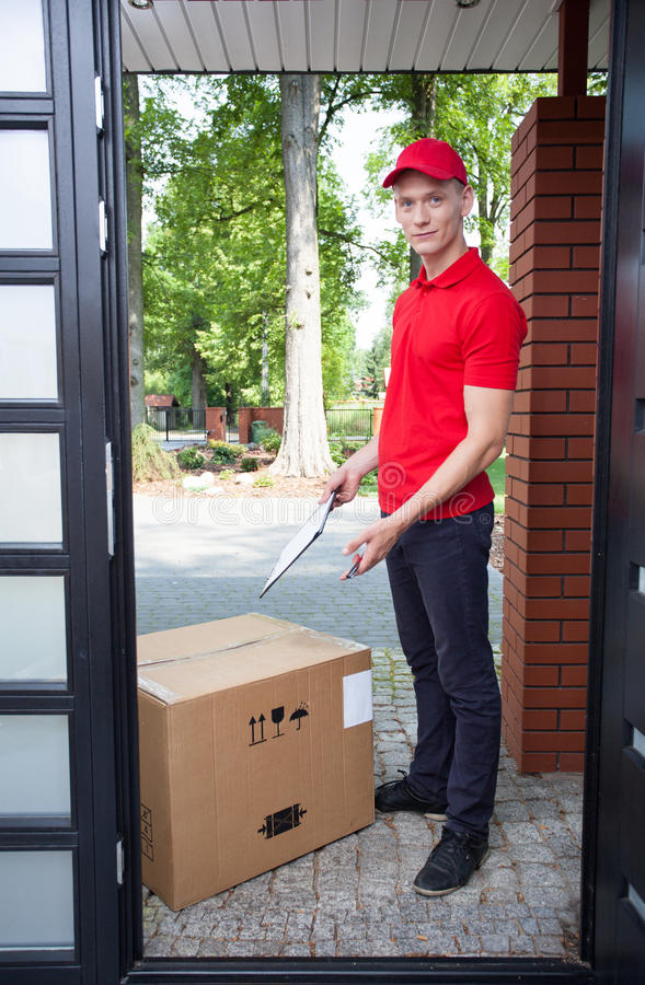 Delivery man with a big box. Delivery guy leaving a large package at doorstep stock photos