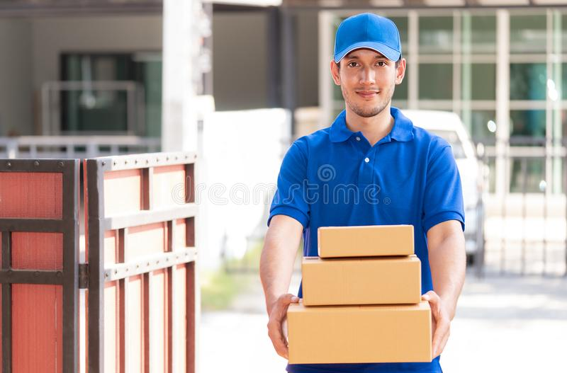 Delivery man in blue handing packages royalty free stock photography