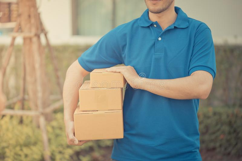 Delivery man in blue handing packages stock photography