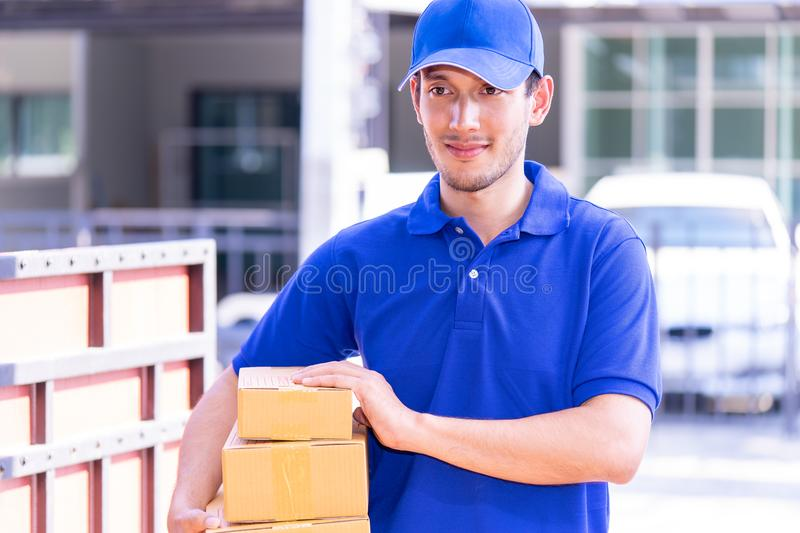 Delivery man in Blue handing packages to home royalty free stock photos