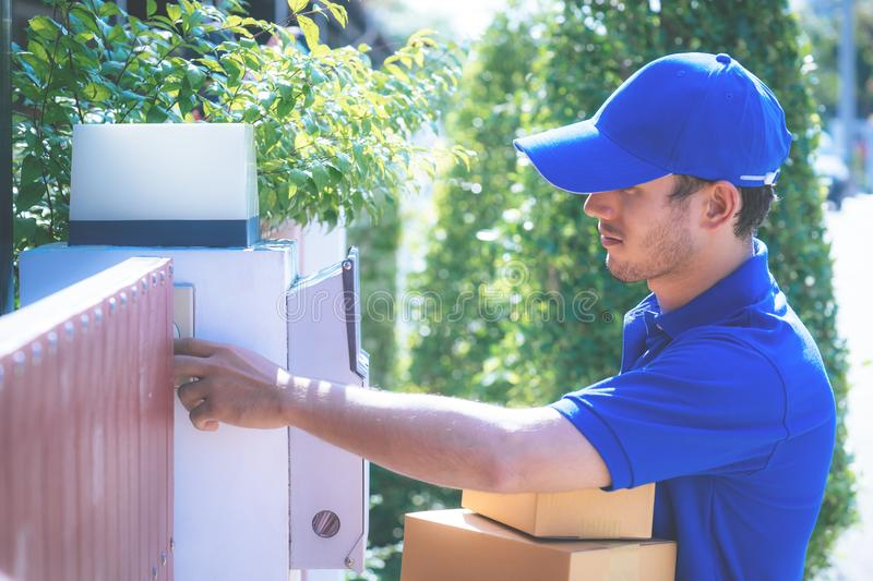 Delivery man in Blue handing packages to home stock images
