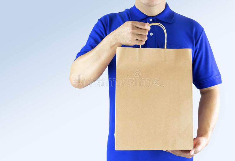Delivery man in blue uniform and holding paper bag with delivering package on gray background. Concept fast food delivery service royalty free stock image